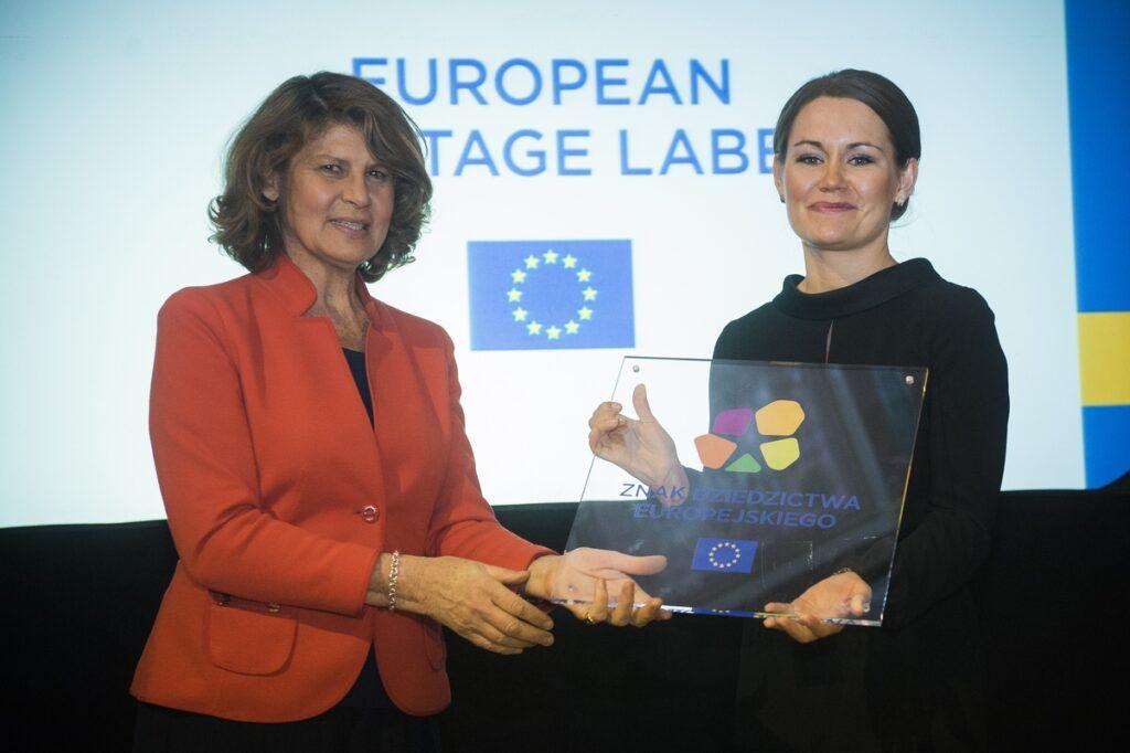 Uśmiechnięta Dyrektor Katarzyna Mieczkowska otrzymuje Znak Dziedzictwa Europejskiego z rąk kobiety po jej prawej stronie.