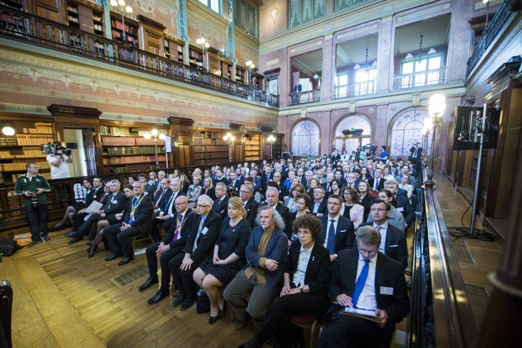 Widok na salę pełną siedzących na krzesłach ludzi.